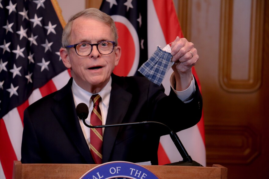Gov. Mike DeWine holds up a face mask at a press conference April 6, 2020.
