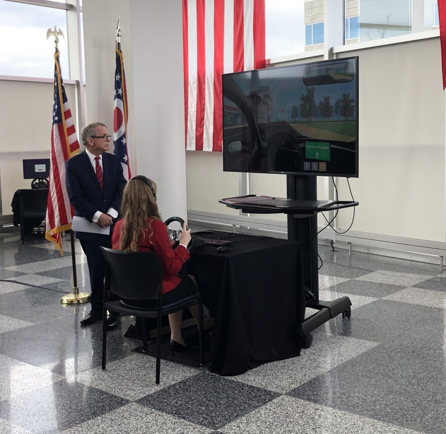 photo of dewine watching a teenager practice driving using the new virtual tool