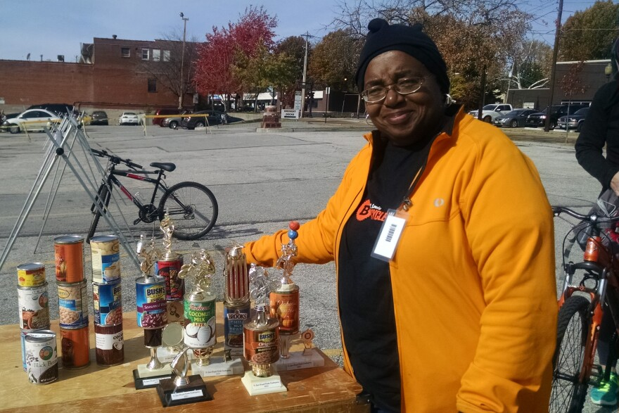 BWorks board president Wilma Schmitz shows off the special Cranksgiving trophies created from old food cans and bicycling awards.