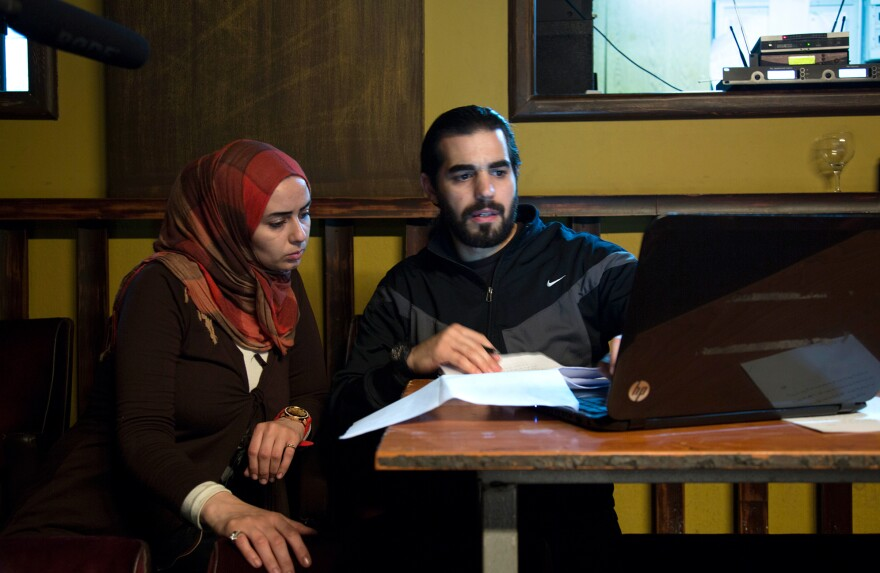 Mona, left, sits next to Syrian playwright Mohammad al-Attar as he gives her some instructions during rehearsal.