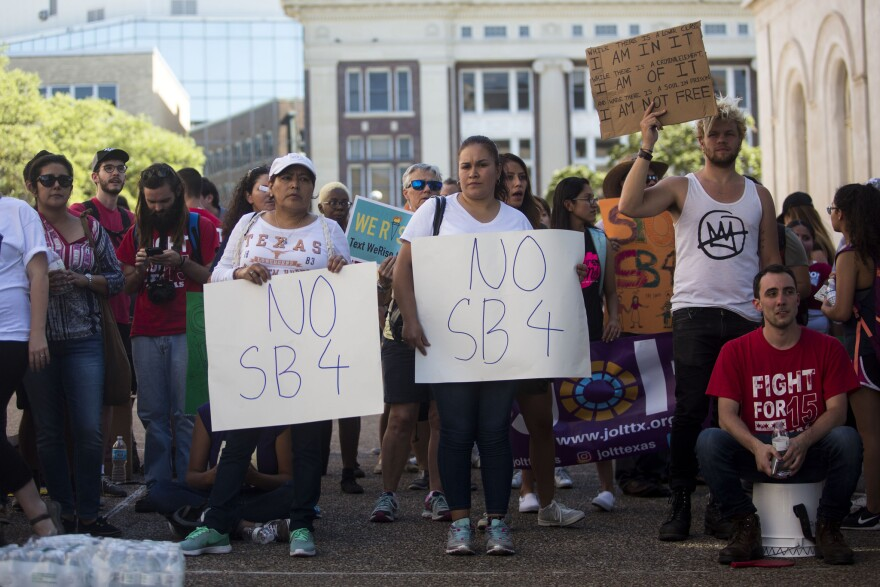 Demonstrators outside the Office of the Governor support a sit-in protest led by City Council Member Greg Casar and dozens of others to protest SB 4.