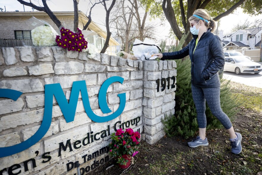 "Katie Cukerbaum lays flowers and a card on a memorial outside the Children's Medical Group facility, honoring the life of Dr. Katherine Lindley Dodson, who was shot during a six-hour hostage situation the night before. ""It's just a tragedy,"" said Cukerbaum, whose one-and-a-half-year-old son was a patient of Dr. Dodson."