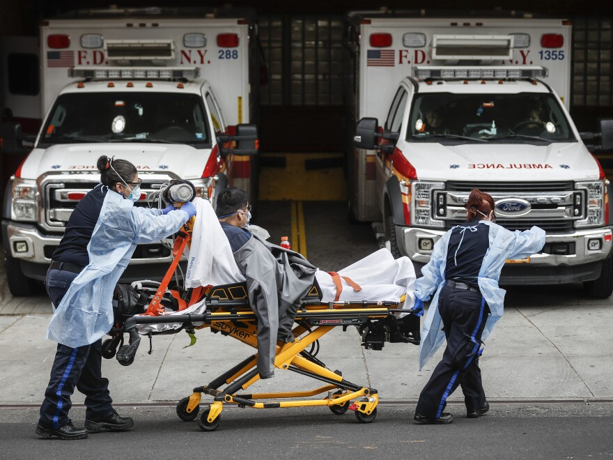 Patients are brought into Wyckoff Heights Medical Center by staff wearing personal protective gear due to COVID-19 concerns on Tuesday in the Brooklyn borough of New York.