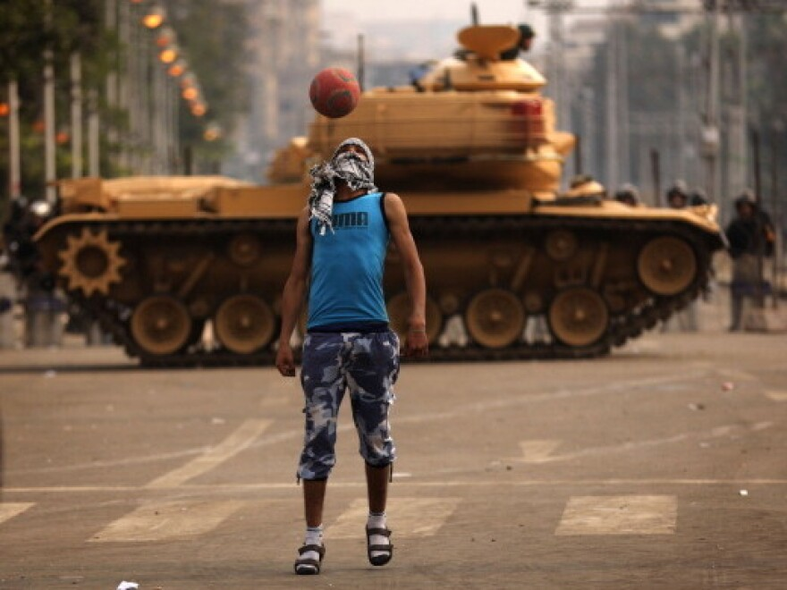 A supporter of the opposition to Egyptian President Mohamed Morsi was playing soccer near a Republican Guard tank earlier today  outside the presidential palace in Cairo. Egyptians are being called to vote over the next two weekends in a referendum on a draft constitution.
