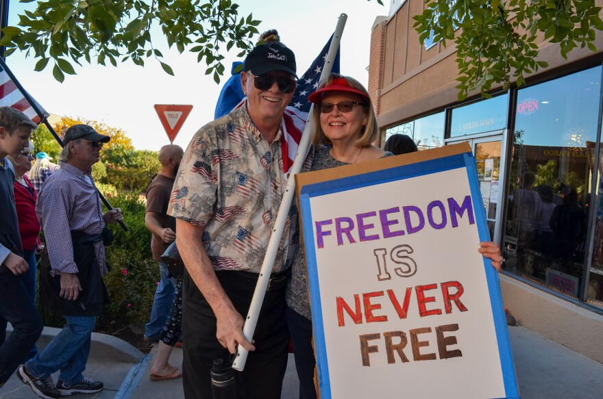"""A photo of Richard and Janet Falconer holding an American flag and sign that says """"freedom is never free."""""""