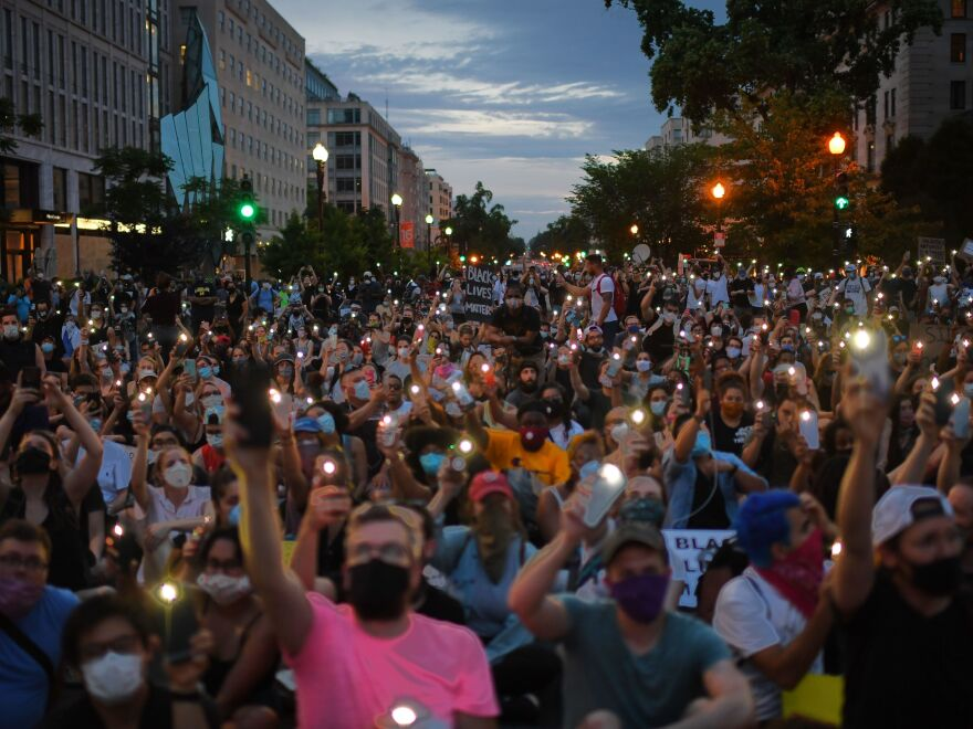 Protesters hold up their phones during a demonstration near the White House over the death of George Floyd.