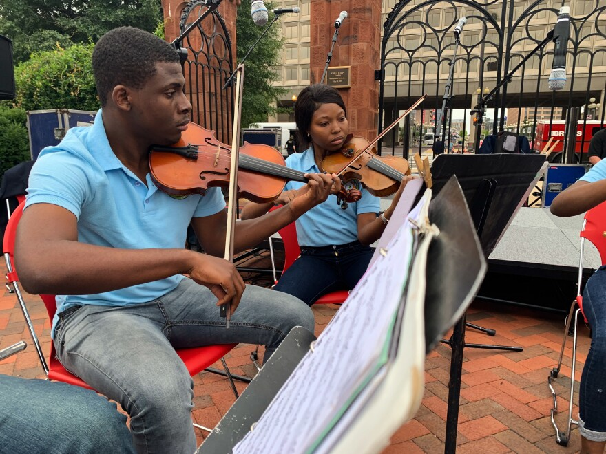 A chamber ensemble from Holy Trinity Music School performs pieces by Haitian composers on the National Mall. Pictured: Violinists Kerdy Freud Exe Jeunesse (left), 17, and Hilary Herva Philistin, 19.