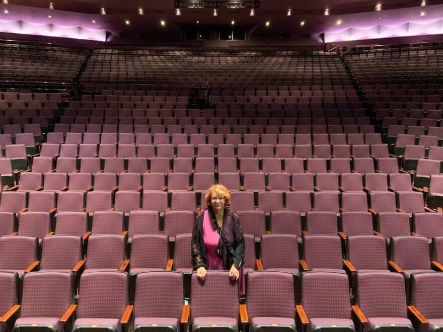 Woman stands in an empty theater with purple seats.