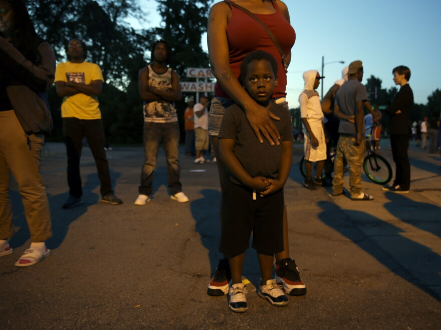 Jeremiah Parker, 4, stands in front of his mother, Shatara Parker, as they attend a protest in Ferguson, Mo. Nights of unrest have vied with calls for calm in the St. Louis suburb where Michael Brown, an unarmed black teenager, was killed by police.