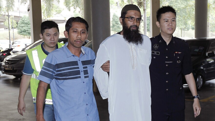 Danish national Salah Salem Saleh Sulaiman (second from right) is escorted by police on Monday as he arrives at a courthouse in Kuala Lumpur, Malaysia.