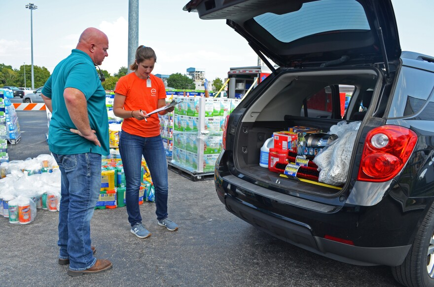 Kayleigh Hogan and Ron Criddle help load vehicles with household supplies provided by the chemical company Covestro to its employees after Hurricane Harvey.