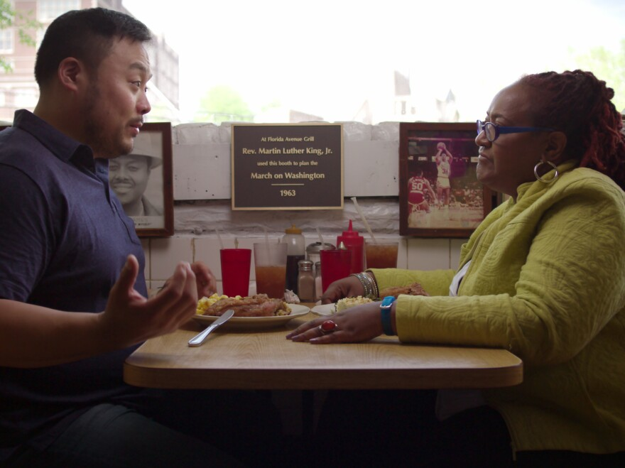 """A still from the Netflix series """"Ugly Delicious"""" shows a man and woman seated across from each other at a casual eatery with plates of food in front of them.  Neither is eating as they engage in conversation."""