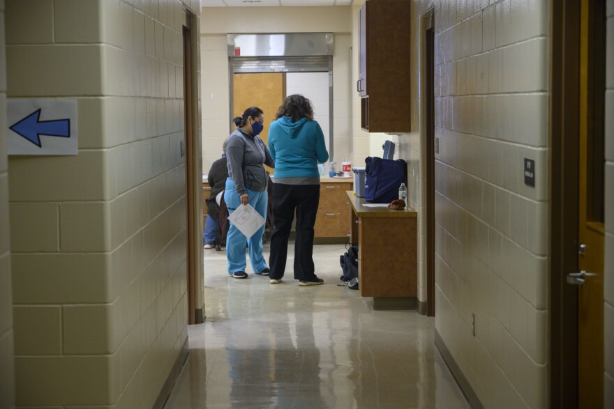 Tama County Public Health Executive Director Shannon Zoffka (right) speaks to a volunteer at the county's COVID-19 vaccination clinic at the former Girls State Training School in Toledo, Iowa.