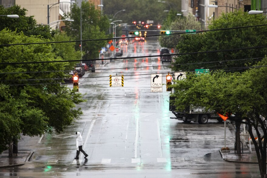 A lone person crosses the street in the rain in Austin.