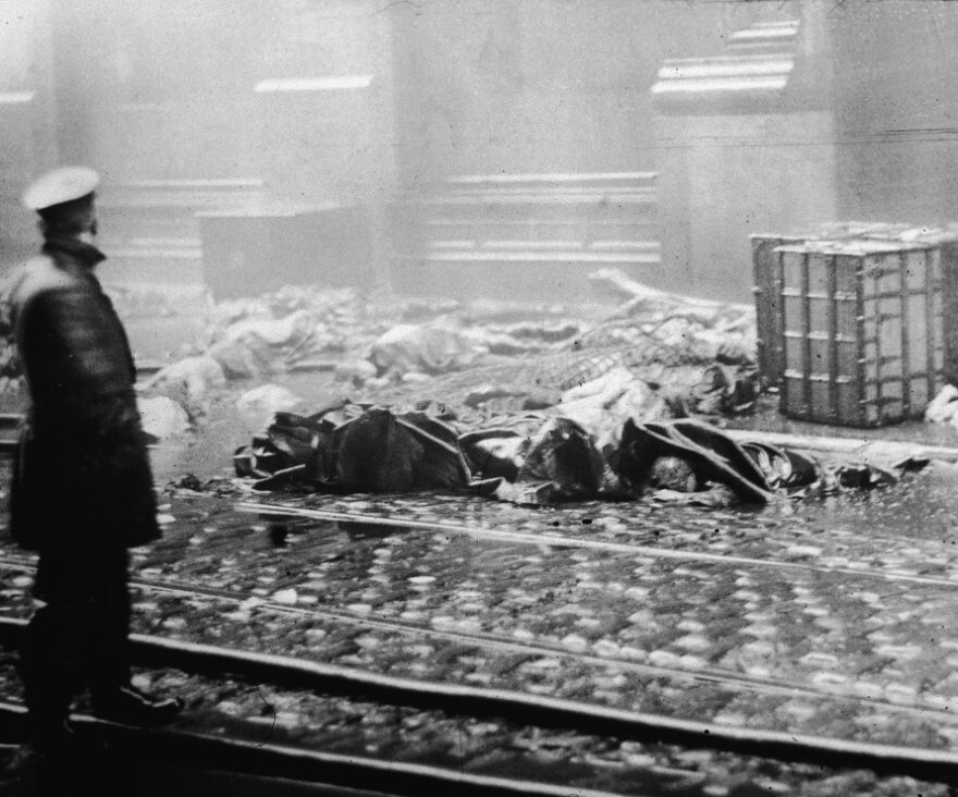 <strong>The Aftermath:</strong> A policeman stands in the street below the factory after the fire. The tragedy led to legislative reforms on a national level and spurred support for organized labor.