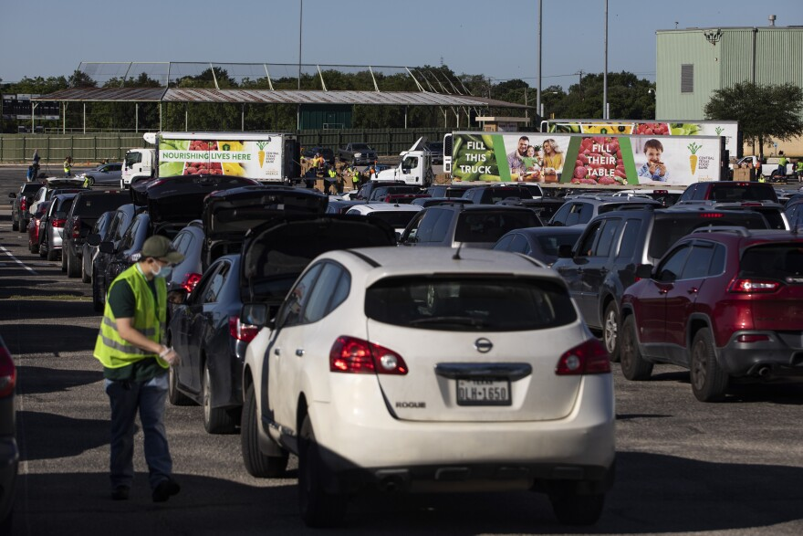 Cars wait in line at a Central Texas Food Bank emergency relief food distribution at Toney Burger Center in April.
