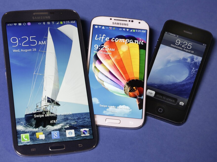 The Samsung Galaxy Mega (from left), Samsung Galaxy S4 and Apple iPhone 5 are shown. Apple is expected to announce larger models of its smartphone on Tuesday.