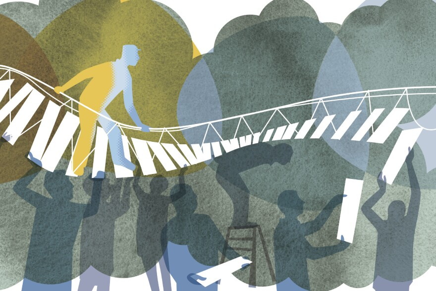 Man walking on bridge supported by co-workers below