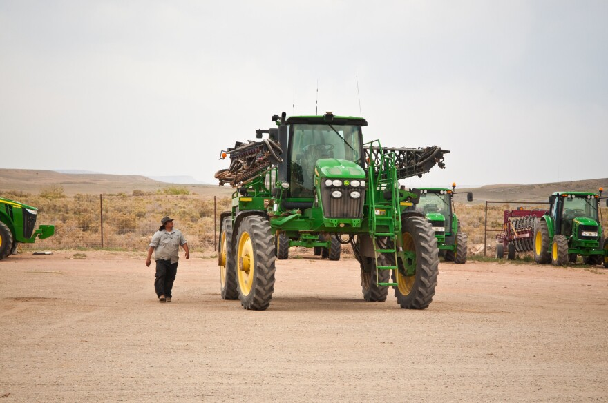 A man walks toward a large tractor on a dirt surface.