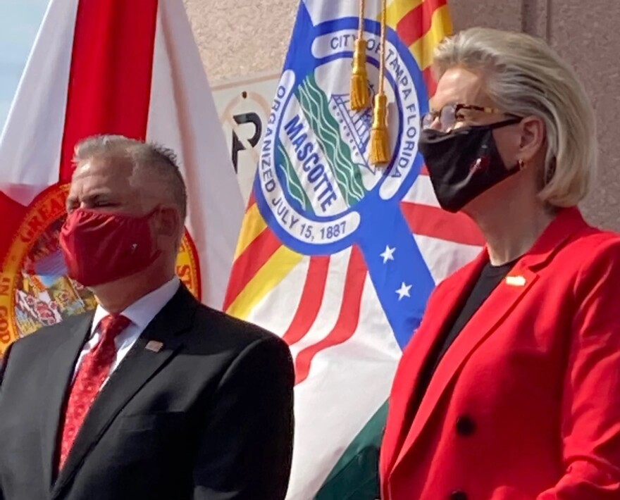 man and woman wearing masks stand in front of Tampa and Florida flags