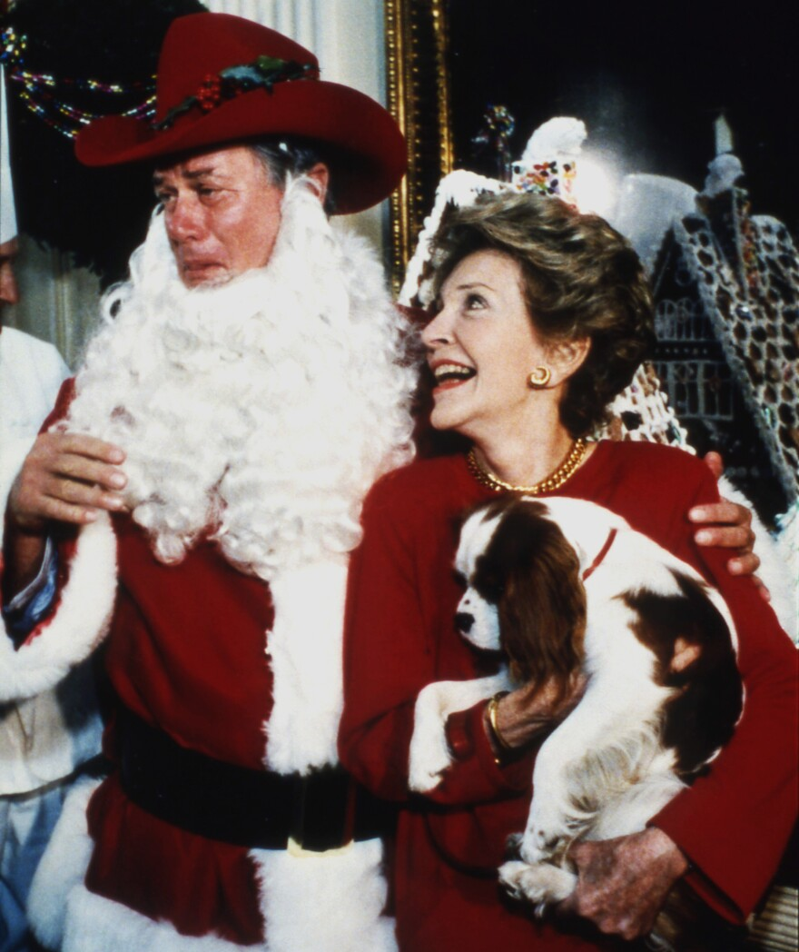First lady Nancy Reagan holds Rex the dog and looks up at Larry Hagman, the actor who played J.R. Ewing on the hit 1980s show <em>Dallas</em> and who is dressed as Santa at the White House, Dec. 9, 1985.
