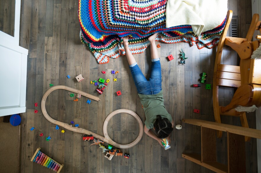 Overhead view girl playing with cellphone on hardwood floor in bedroom