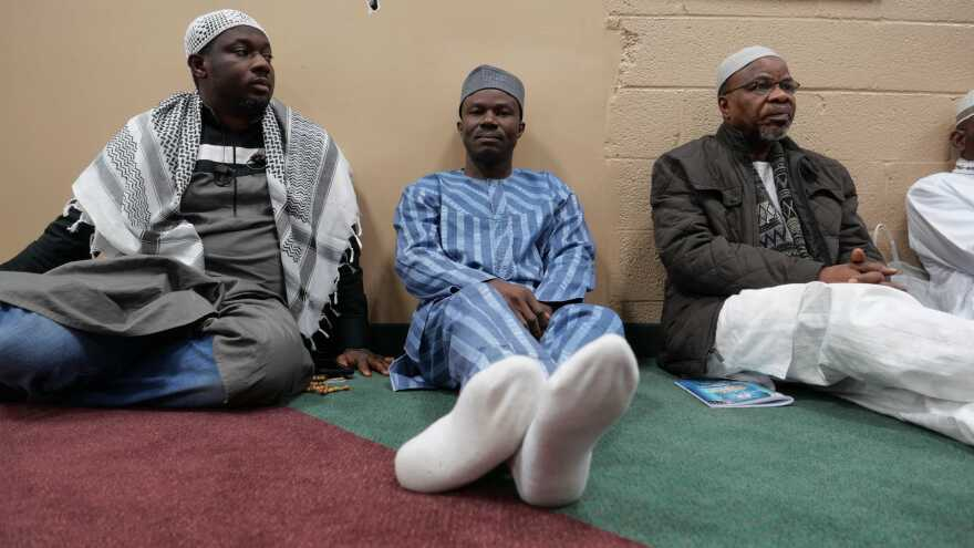 Rafiu Aremu (center) sits alongside others at a Nigerian mosque just outside D.C. Aremu wonders whether the real purpose behind the travel ban is to reduce the inflow of immigrants from Africa to the U.S.