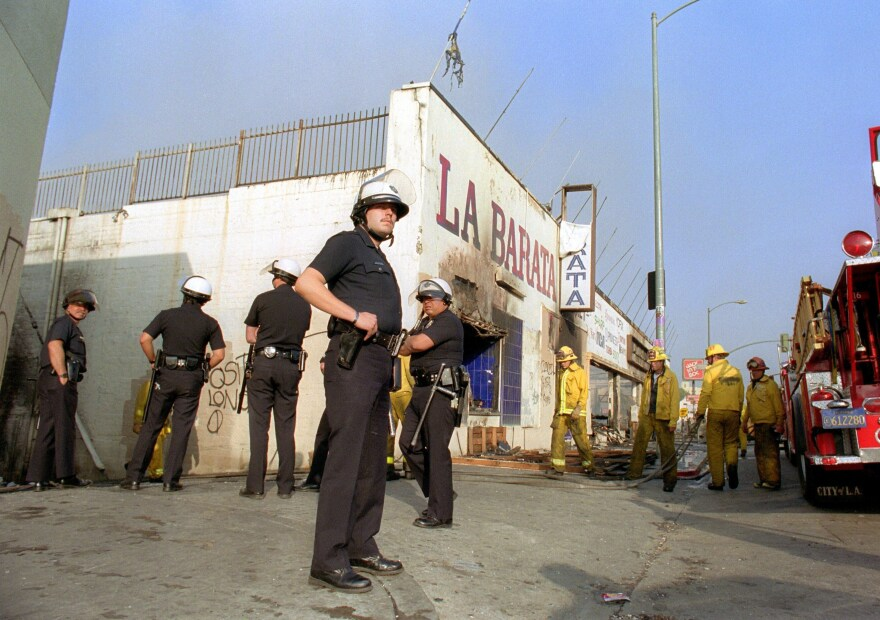 Los Angeles police officers in riot gear stand guard at a grocery store that had been burned down near downtown Los Angeles on April 30, 1992.