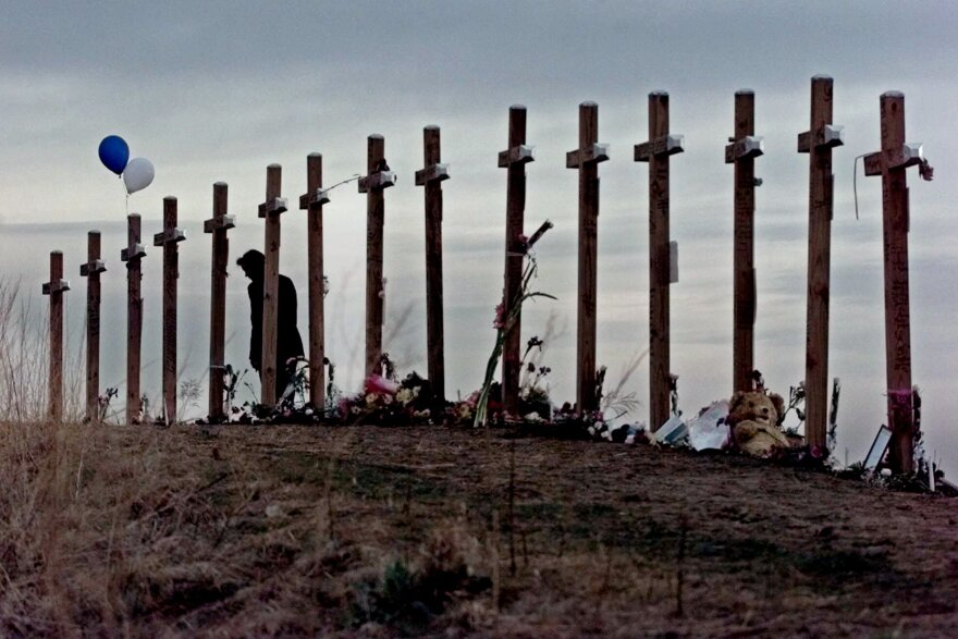 A woman looks at 15 crosses posted on a hill above Columbine High School in Littleton, Colo. in remembrance of the 15 people who died during a shooting rampage at the school in 1999.