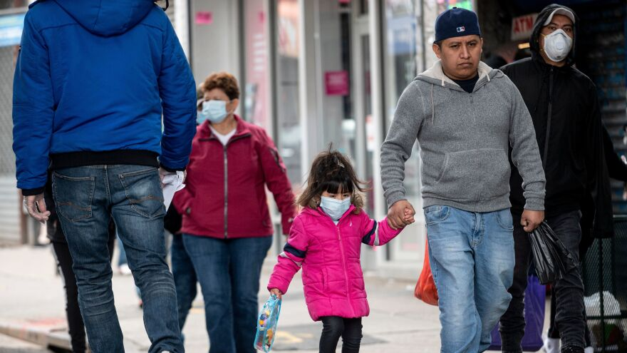 People, some wearing masks, walk down a street in the Corona neighborhood of Queens in New York on Tuesday.