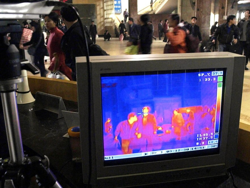 The full-body infrared scanner depicts body temperature with colors on a computer screen. China used the device during the 2003 outbreak of the respiratory virus SARS (pictured, above). Some airports have turned to the scanner as part of Ebola screening.