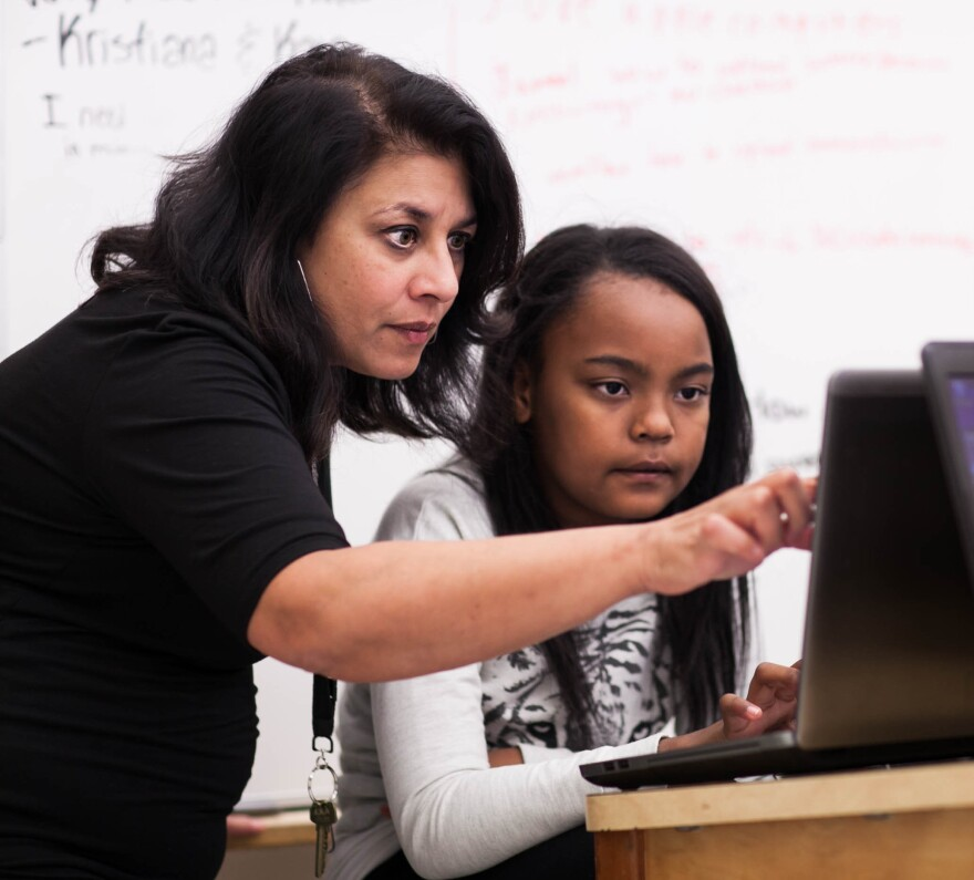Incubator founder and sixth-grade teacher Sujata Bhatt assists student Elise Mayfield with a Minecraft assignment. Much of the classroom learning is done independently or as a group, with the teacher stepping in as needed.