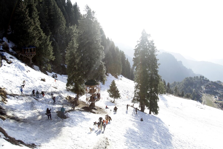 Families play on a ski slope.