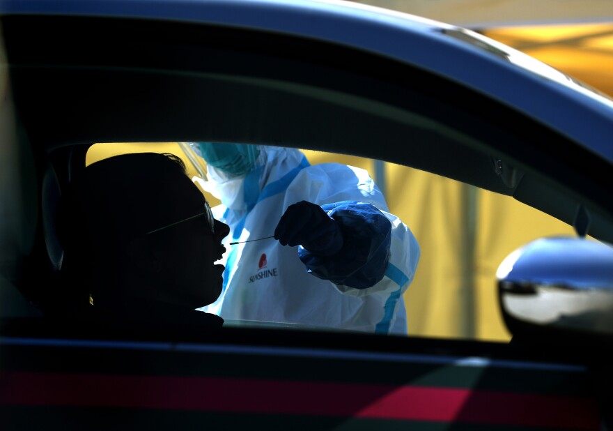 After an initial verbal screening, one driver at a time gets a COVID-19 nasal swab test from a garbed health worker at a drive-up station in Daly City, Calif.