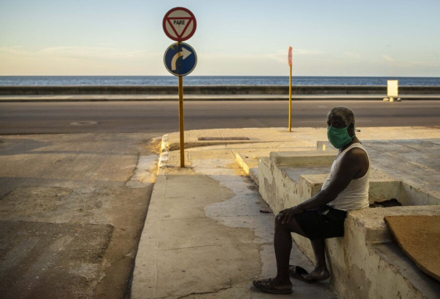 A man wearing a protective mask sits alone this week on Havana's seawall, the Malecon, as a strict curfew to control COVID-19 goes into effect.