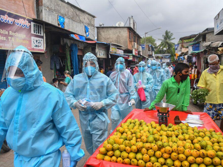 Medical staff along with Hindu hardline group Rashtriya Swayamsevak Sangh (RSS) volunteers walk through a market for a door-to-door medical screening in Mumbai on June 17, 2020.