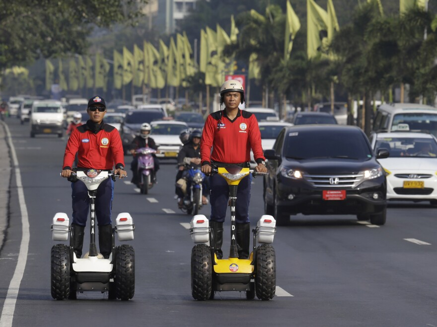 MMDA (Metro Manila Development Authority) traffic enforcers patrol a street on their Segway vehicles in a 2011 photo. During a visit by Pope Francis next week, they are being asked to wear adult diapers so they won't have to leave their posts.