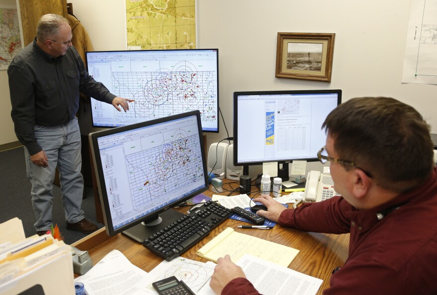 Charles Lord (left), senior hydrologist, explains the mapping procedure used by the Corporation Commission to chart fault lines, earthquakes and disposal wells, as Jim Marlatt, oil and gas specialist, looks on from his desk in Oklahoma City on Nov. 30. State regulators have taken steps to try to curb the number of quakes.
