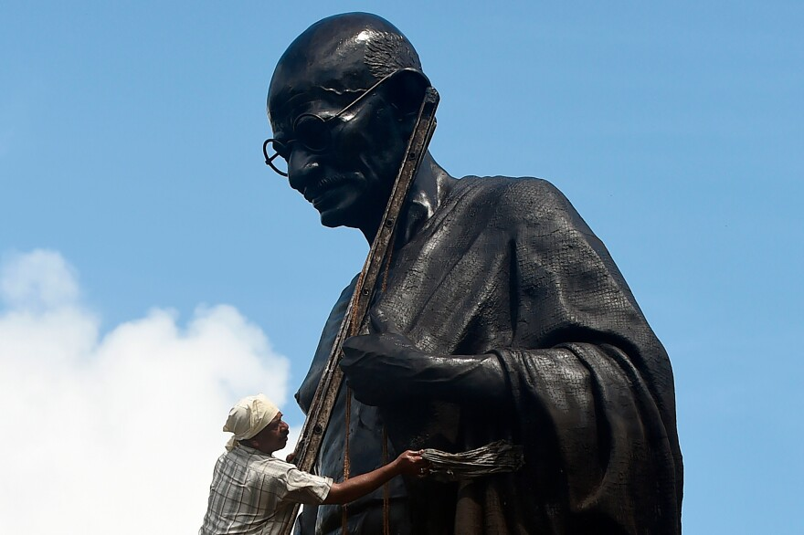 A worker cleans a statue of Gandhi in Mumbai on Tuesday, the day before the 150th anniversary of the birth of the Indian philosopher and anti-colonial activist.