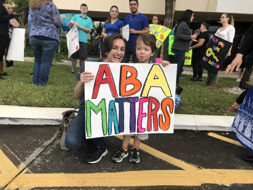 A therapist poses with a young boy at a state health meeting in Tampa.