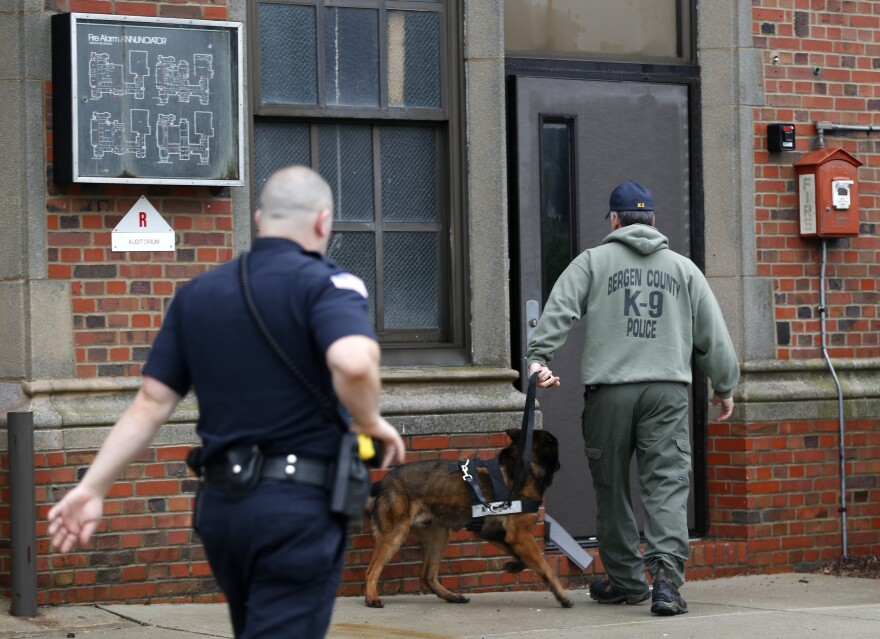 A Bergen County, N.J., police officer (right) walks with a police dog into Teaneck High School, where 62 students were arrested during an overnight break-in on Thursday in Teaneck.