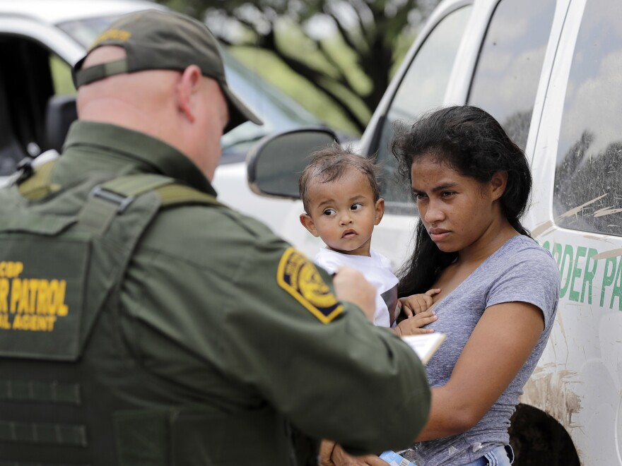 President Trump's zero tolerance policy left the CBP struggling to process the number of people it detained — and the agency says it will temporarily stop turning immigrant parents over to prosecutors. Here, a mother migrating from Honduras holds her 1-year-old child as she surrenders to border agents on Monday. The two had illegally crossed the border near McAllen, Texas.
