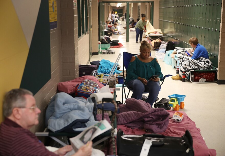 Bob Cavanagh, left, and Linda Moore, center, wait in an evacuation shelter setup at the Conway High School for the arrival of Hurricane Florence on Thursday in Conway, S.C. Many schools in the area have closed or been converted to shelters for residents in the region.