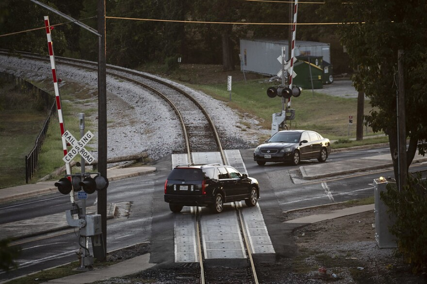 Vehicles drive over the railroad crossing in the Rosewood neighborhood of East Austin.
