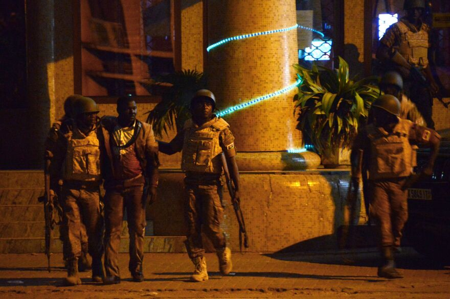 Burkinabe soldiers evacuate an injured man from the Splendid hotel during an attack by Al-Qaeda-linked gunmen late Friday in Ouagadougou, Burkina Faso. Burkina Faso's troops, supported by French special forces, battled the attackers early Saturday morning and freed more than 120 hostages, officials say.
