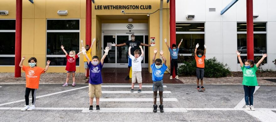 Young children with face masks standing in front of the Boys & Girls Club in Sarasota.