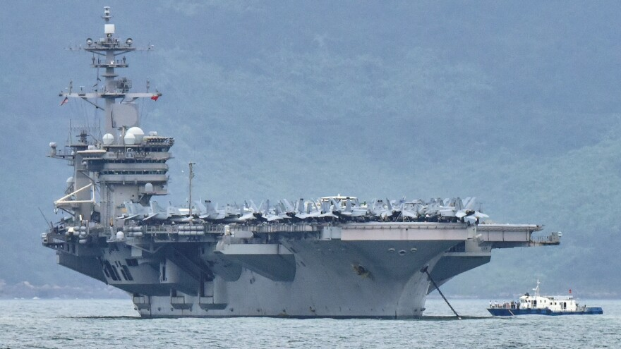 "The acting secretary of the Navy is seeking a more thorough review of ""decisions of the chain of command surrounding the COVID-19 outbreak aboard the USS Theodore Roosevelt."" The aircraft carrier is seen here as it enters the port in Da Nang, Vietnam, last month."