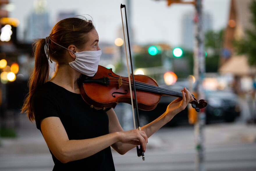 Stasia Erickson wears a mask while playing a violin on South Congress on May 22.