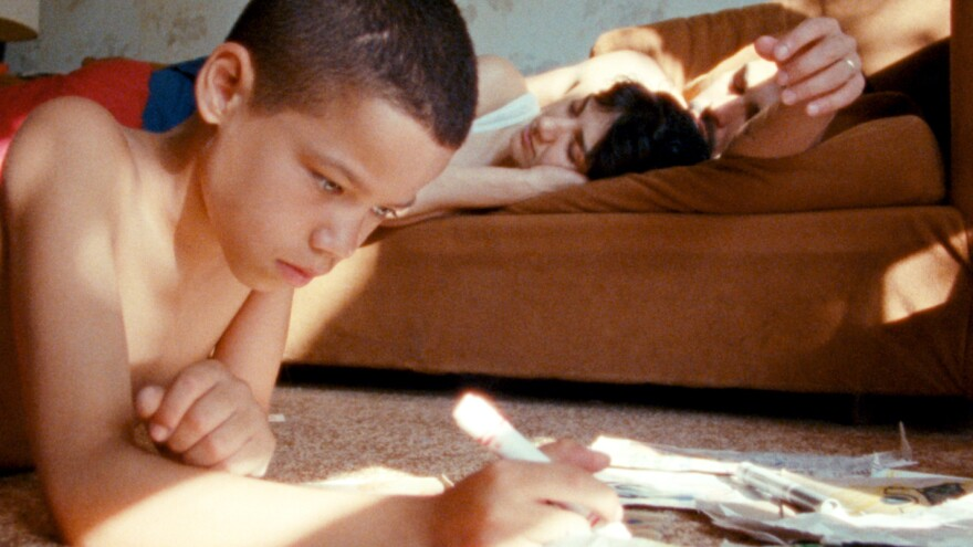 L to R: Jonah (Evan Rosado) draws while Ma (Sheila Vand) and Paps (Raul Castillo) drowse, in <em>We the Animals</em>.