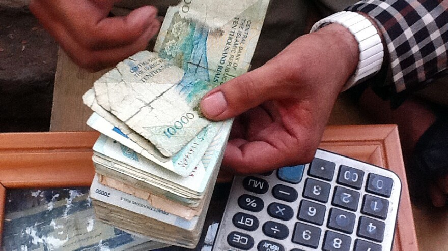 A money-changer in the Afghan city of Herat counts a stack of Iranian bills. More and more Iranian currency is being brought in by smugglers to exchange for dollars, which then go back to Iran.